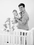 Portrait noir et blanc de père montrant à son bébé le nouveau berceau Image stock