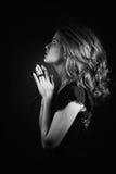Portrait noir et blanc dramatique d'une émergence de prière ou de pensée de femme d'un fond noir Image stock