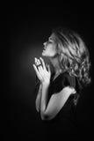 Portrait noir et blanc dramatique d'une émergence de prière ou de pensée de femme d'un fond noir Photos libres de droits