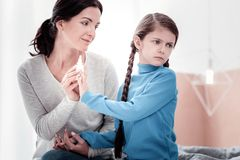 Portrait of noisy child being against treatment. Do not worry. Portrait of little pleasant girl keeping her hand against nasal drops while her mother calming her royalty free stock photo