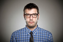 Portrait of a normal boy with glasses over grey background. Stock Image