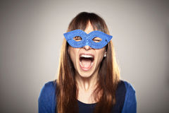 Portrait of a normal girl screaming with a blue mask Royalty Free Stock Photos