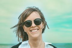 Portrait of a normal girl with smiling sunglasses on the beach. royalty free stock photography