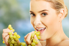 Portrait of nude woman eating grapes Royalty Free Stock Photos