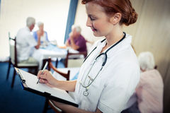 Portrait of a nurse with clipboard. In the retirement house Royalty Free Stock Photo