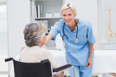 Portrait of nurse consoling patient sitting on wheelchair Stock Photos