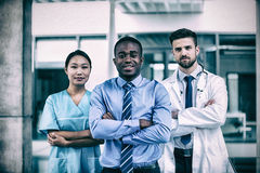 Portrait of nurse and doctor with businessman. Standing in hospital stock image