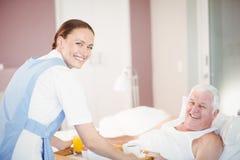 Portrait of nurse offering breakfast to senior man lying on bed Stock Photos