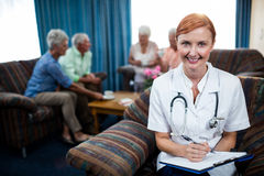 Portrait of a nurse with pensioners in background Stock Photo