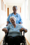 Portrait of nurse pushing patient sitting in wheelchair Royalty Free Stock Image