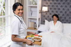 Portrait of nurse serving breakfast to patient at home Royalty Free Stock Photos
