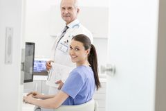 Portrait of nurse using laptop at desk with senior doctor in clinic stock images