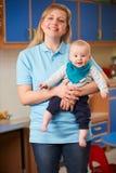 Portrait Of Nursery Worker Holding Baby Stock Photos