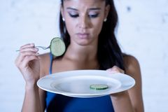 Depressed dieting woman holding folk looking at small green vegetable on empty plate stock photos