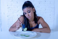 Depressed dieting woman holding folk looking at small green vegetable on empty plate royalty free stock photo
