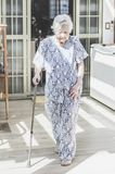 Japanese descendant grandma walking with the help of a walking s. Portrait of a obaasan grandma with difficulty to walk because of the aged legs. Japanese Stock Photography