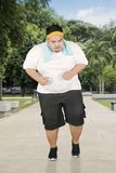 Obese man doing run speed exercises in park royalty free stock image