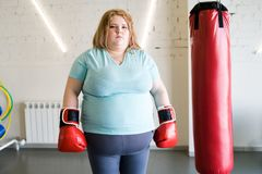 Obese Female Boxer. Portrait of obese woman wearing boxing gloves posing next to punching bag and looking at camera, copy space Royalty Free Stock Photos