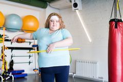 Obese Woman Working Out with Hula Hoop. Portrait of  obese young woman exercising with hula hoop during weightloss training in gym, copy space Royalty Free Stock Photo