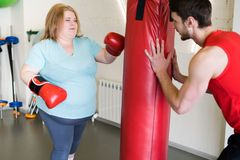 Obese Woman Boxing in Gym. Portrait of obese young women hitting punching bag in gym during personal training with fitness instructor Stock Photos
