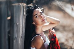 Free Portrait Of A Beautiful Black Haired Girl In A White Vintage Dress Standing Near Wood Fence.Young Woman Model Posing In A Russian Stock Photo - 145497820