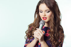 Portrait Of A Beautiful Elegant Girl Singer Brunette With Long Hair With A Microphone In His Hand Singing A Song
