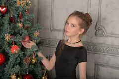 Portrait Of A Beautiful Pensive Girl In Black Near The Christmas Tree At Christmas Stock Photo