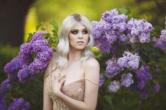 Portrait Of A Beautiful Sensual Young Blond Woman In Spring. Blossoming Spring Garden. Young Girl In A Gold Dress