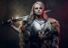 Portrait Of A Beautiful Warrior Woman Holding A Sword Wearing Steel Cuirass And Fur. Fantasy Fashion. Cosplayer As Ciri Royalty Free Stock Image