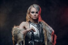 Portrait Of A Beautiful Warrior Woman Holding A Sword Wearing Steel Cuirass And Fur. Fantasy Fashion. Cosplayer As Ciri Stock Photography