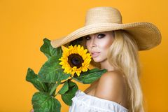 Free Portrait Of A Beautiful Woman With Long Blond Hair, Wearing A White Dress, Holding Sunflowers. Royalty Free Stock Image - 122016116