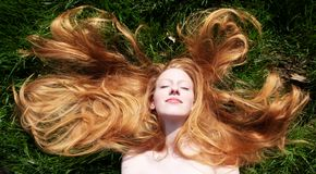 Portrait Of A Beautiful Young Sexy Red-haired Woman, Lying In The Spring Sun, Relaxing On The Green Grass, The Red Hair Draped Royalty Free Stock Photography