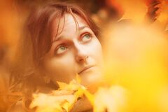 Free Portrait Of A Girl Close-up Through The Autumn Foliage. A Woman`s Face In A Halo Of Yellow Leaves. Copy Space Stock Photos - 198171803