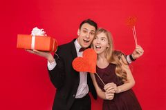 Portrait Of A Happy Couple, Man Holding Paper Hearts, On Red Background, Lovers Day Concept Royalty Free Stock Image