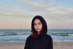 Free Portrait Of A Model In A Fashionable Jacket At Sunset By The Sea. Teenager In A Black Hoodie And The Sea. 9 Years Old Stock Images - 186384084