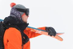 Portrait Of A Professional Athlete Skier In An Orange Jacket Wearing A Black Mask And With Skis On His Shoulder Looks To Stock Image