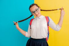 Portrait Of A Schoolgirl In Glasses With Books Textbooks On A Yellow Blue Background In The Studio Stock Photos