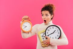 Portrait Of A Shocked Pretty Woman Holding Alarm Clocks Royalty Free Stock Photography
