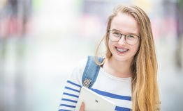 Free Portrait Of A Smiling Beautiful Teenage Girl With Dental Braces. Young Schoolgirl With School Bag And Tablet Device Stock Images - 144665224