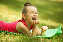 Free Portrait Of A Smiling Little Girl, Lying On Green Royalty Free Stock Images - 45911279