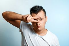 Portrait Of A White Man On A Light Background, Gesture Two Fingers Near The Eyes. The Concept Of Body Language, Expression Of Stock Image