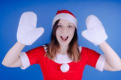 Portrait Of A Young Girl Dressed As Santa Claus On A Blue Background. Happy New Year And Merry Christmas! Stock Photos