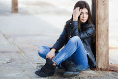 Portrait Of A Young Woman Sitting On The Sidewalk. Stock Photos