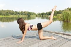 Portrait Of A Young Woman Stretching On A Pier At The Pond. Royalty Free Stock Images