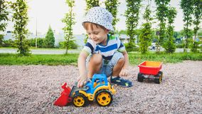 Free Portrait Of Adorable 3 Years Old Toddler Boy Playing With Toy Truck With Trailer On The Playground At Park. Child Royalty Free Stock Image - 148448146