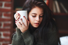 Free Portrait Of Beautiful Girl With Dark Hair In A Green Sweater With A Cup Of Coffee Or Tea At Home. Close-up Royalty Free Stock Image - 87267266