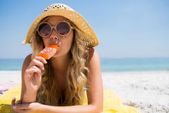 Free Portrait Of Beautiful Woman Eating Popsicle While Relaxing At Beach Stock Image - 92601391