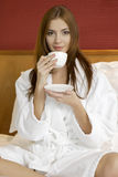 Portrait Of Beautiful Woman With Cup On Bed Royalty Free Stock Images