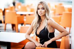 Portrait Of Blond Young Woman With Beautiful Makeup And Hair In A Classic Black Dress Sitting In Outdoor Cafe. Fashion Stock Photos