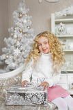 Portrait Of Blonde Little Girl Sits On A Sofa And Touches A Gift Box In Christmas Royalty Free Stock Photography